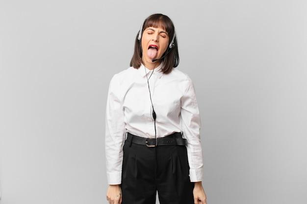 Femme de télévendeur avec une attitude joyeuse, insouciante et rebelle, plaisantant et tirant la langue, s'amusant