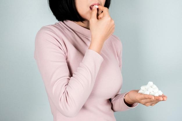 La femme tenait un morceau de sucre et se sentait malade avec des morceaux de sucre.