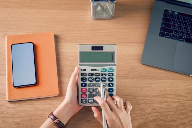Femme tenant et appuyez sur la calculatrice pour calculer les dépenses de revenu et les plans pour dépenser de l'argent au bureau à domicile.