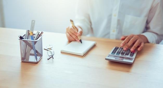 Femme tenant et appuyez sur la calculatrice pour calculer les dépenses de revenu et les plans pour dépenser de l'argent sur le bureau à domicile.