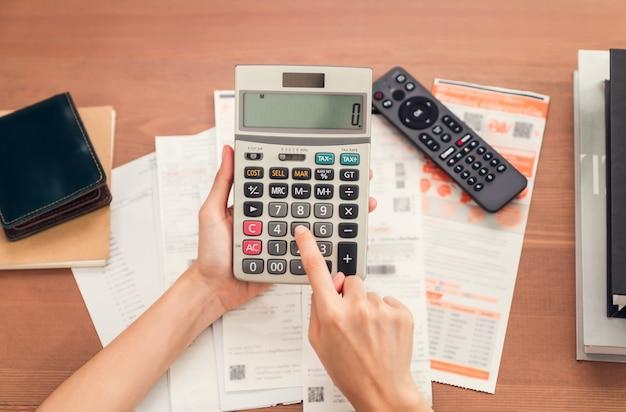 Femme tenant et appuyez sur la calculatrice pour calculer les dépenses de revenu et les plans pour dépenser de l'argent à la maison.