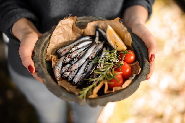Femme tenant une assiette d'anchois frais avec un romarin, des tomates cerises et du citron à l'extérieur.