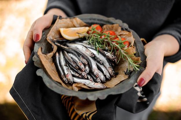 Femme tenant une assiette d'anchois frais avec un romarin, des tomates cerises et du citron avec une serviette rayée noire, blanche et jaune