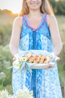 Femme tenant une assiette avec empanadas, cuisine argentine classique.