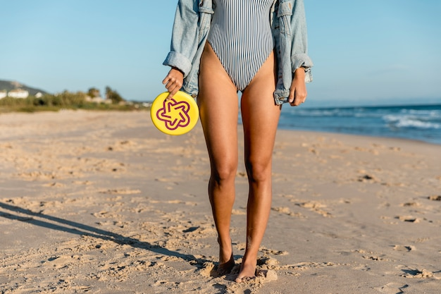 Femme tenant une assiette de frisbee au bord de la mer