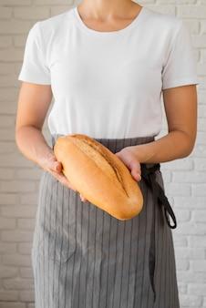Femme tenant une baguette fraîche