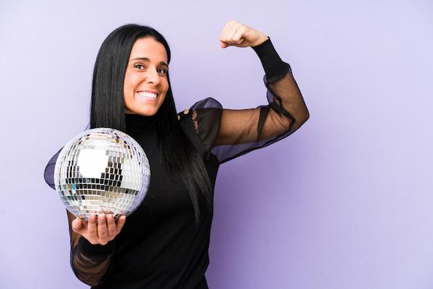 Femme tenant un bal isolé sur violet levant le poing après une victoire, concept gagnant.