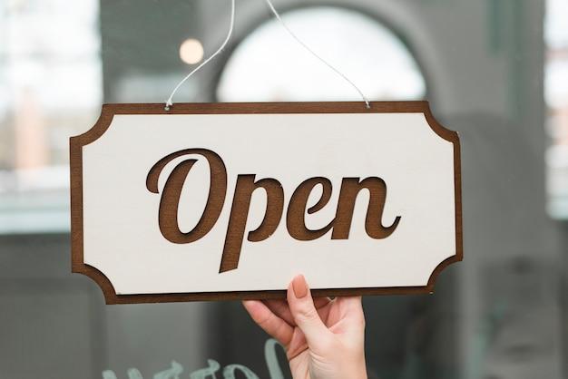Femme tenant une balise ouverte suspendue à un verre de devanture de magasin