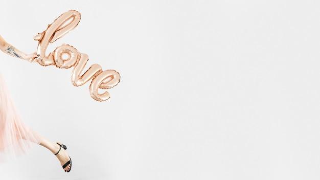 Femme tenant un ballon d'aluminium d'amour et s'éloigner
