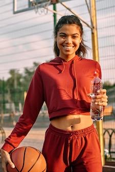 Femme tenant un ballon de basket et une bouteille d'eau