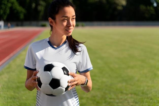 Femme tenant un ballon de football sur le terrain