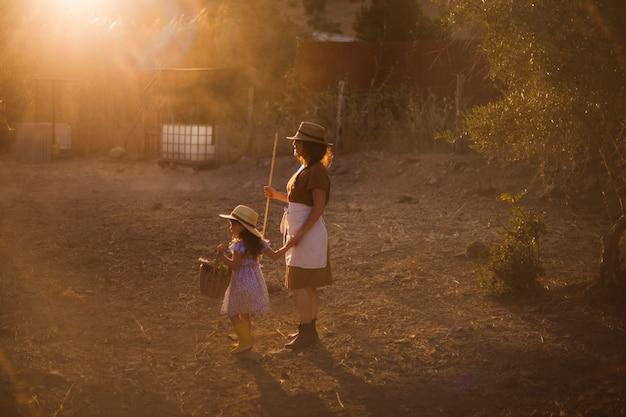 Femme tenant un bâton debout avec sa fille dans le champ