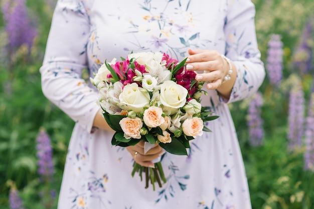Femme tenant un beau bouquet de fleurs aux couleurs vives. d'une main, elle touche la tendresse et la fragilité des fleurs. le bouquet de la mariée lors d'un mariage