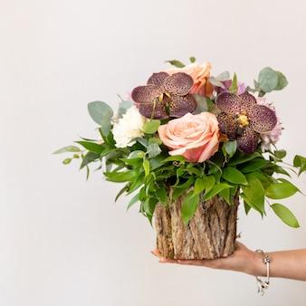 Femme tenant un beau bouquet de fleurs dans le pot en bois