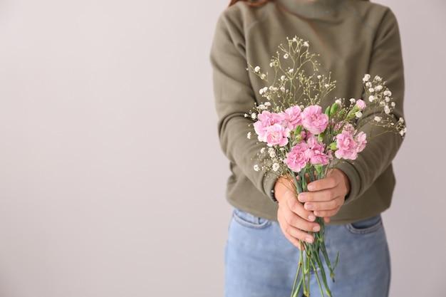 Femme tenant de belles fleurs roses sur gris