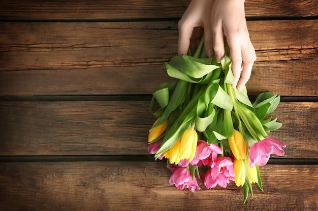 Femme tenant de belles tulipes sur une surface en bois