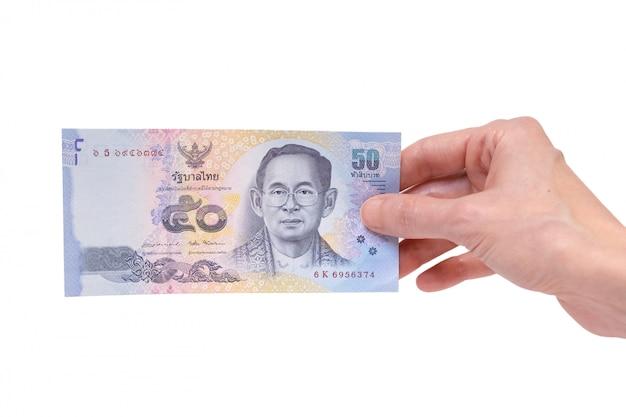 Femme tenant un billet de 50 bahts thaïlandais dans sa main sur un fond blanc