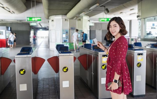 Femme tenant un billet de train à la porte d'entrée