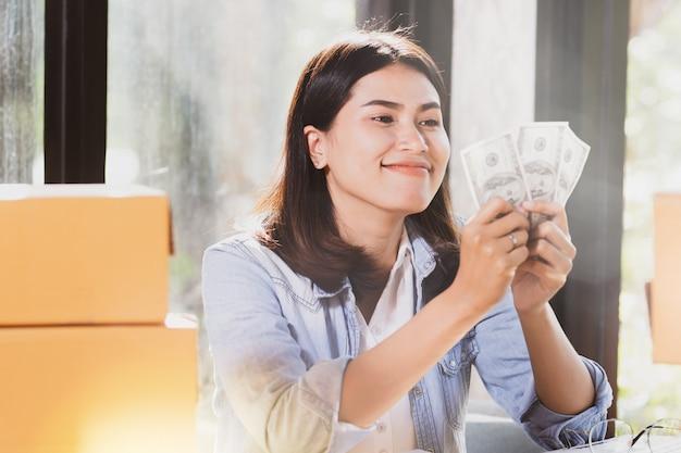 Femme tenant des billets d'argent sourit avec plaisir.