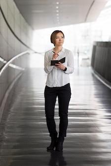 Femme tenant un bloc-notes complet
