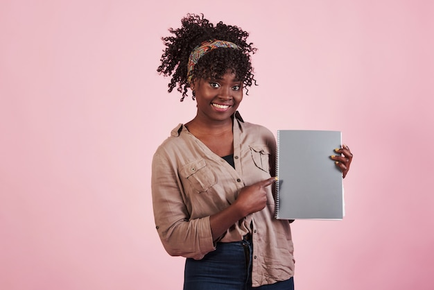 Femme tenant un bloc-notes gris dans ses mains au fond de studio rose
