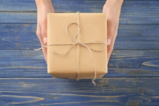 Femme tenant une boîte-cadeau de colis sur fond de bois, vue de dessus
