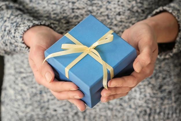 Femme tenant une boîte-cadeau, gros plan