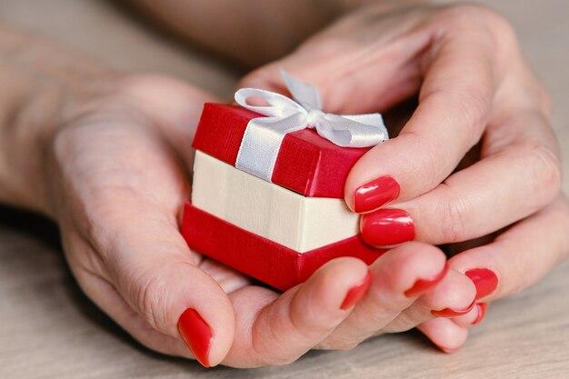 Femme tenant une boîte cadeau rouge