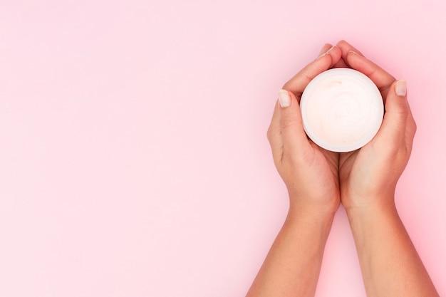 Femme tenant une boîte de crème pour le visage avec espace copie