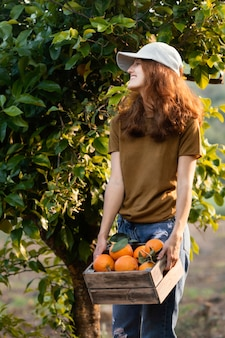 Femme tenant une boîte avec des oranges