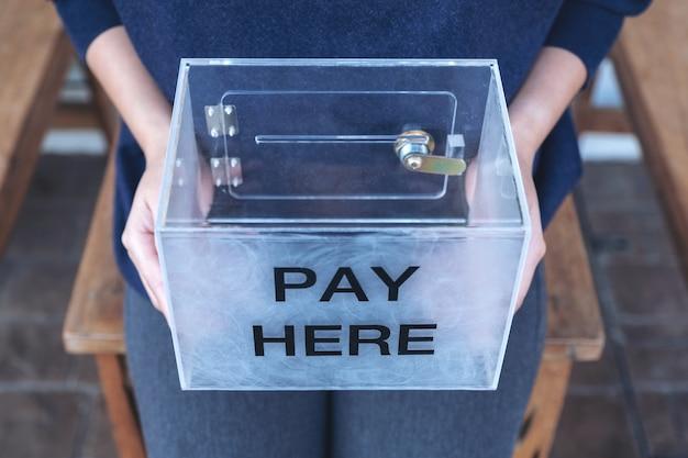 Une femme tenant une boîte de paiement en plastique