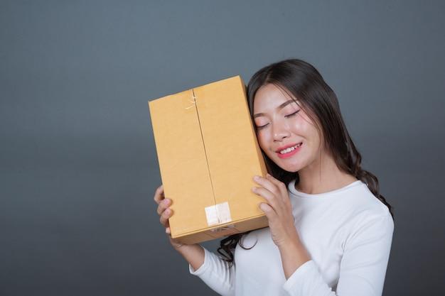 Femme tenant une boîte postale brune fait des gestes avec la langue des signes.