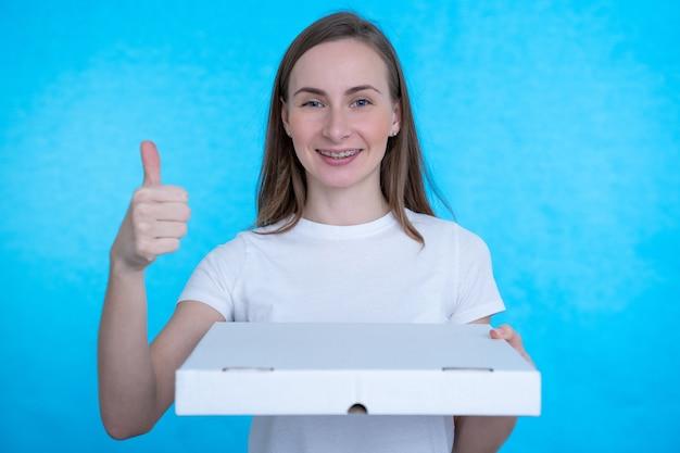 Femme tenant des boîtes à pizza sur un mur bleu avec une expression heureuse