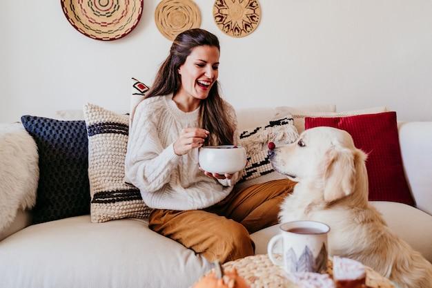 Femme tenant un bol de fruits aux myrtilles et framboises à la maison pendant le petit déjeuner.