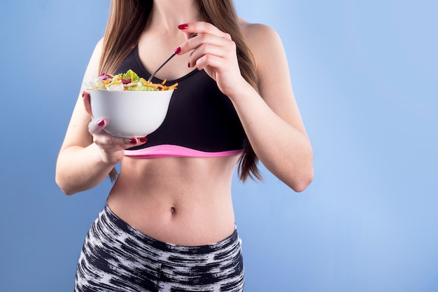Femme tenant un bol avec une salade de légumes