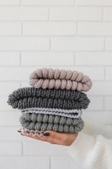 Femme tenant des bonnets tricotés