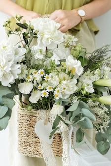 Femme tenant un bouquet de fleurs blanches