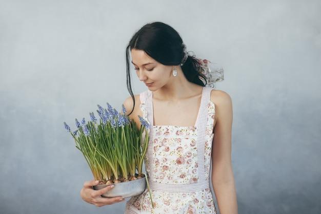 Femme tenant un bouquet de fleurs dans les mains à l'intérieur