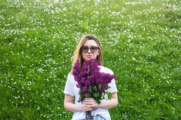 Femme tenant un bouquet de fleurs lilas vives contre l'espace floral vert d'été