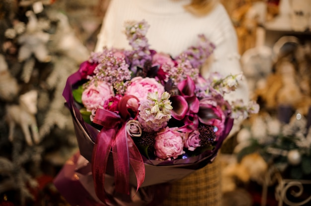 Femme tenant un bouquet de fleurs roses, violettes et cramoisies enveloppées de papier de couleur foncée