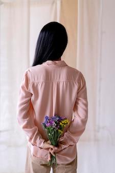 Femme tenant un bouquet de fleurs vue arrière
