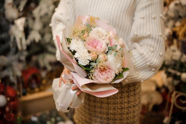 Femme tenant un bouquet de roses pivoine rose tendre décoré de petites branches et feuilles vertes
