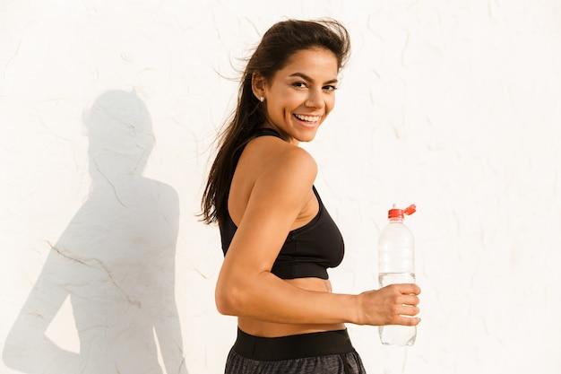 Femme tenant une bouteille avec de l'eau et debout sur le mur, après l'entraînement du matin