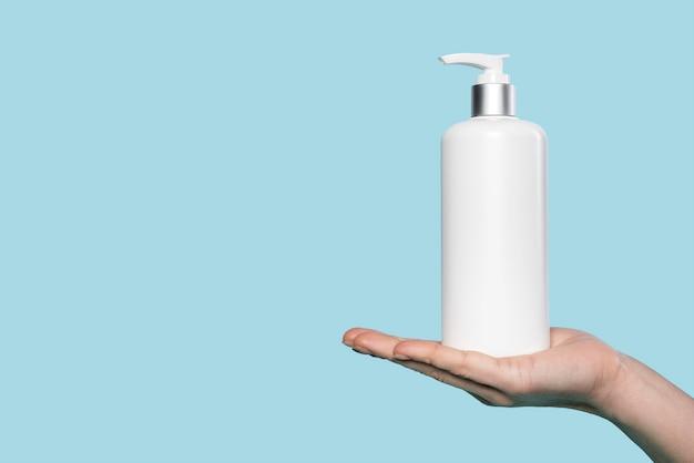 Femme tenant une bouteille de savon liquide