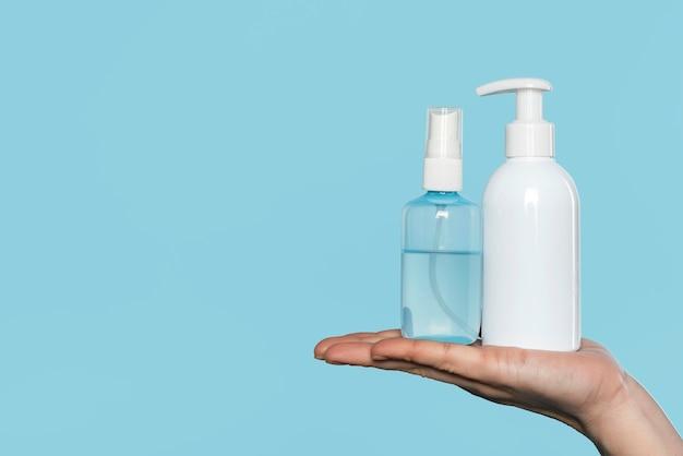 Femme tenant des bouteilles de désinfectant