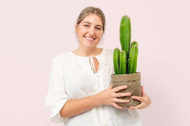 Femme tenant un cactus en pot dans un emballage durable