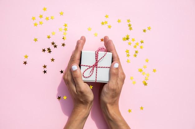 Femme tenant un cadeau et des étincelles