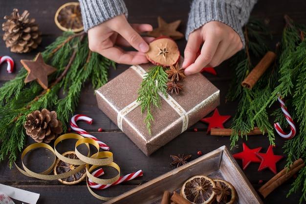 Femme tenant des cadeaux de noël posés sur une table en bois.