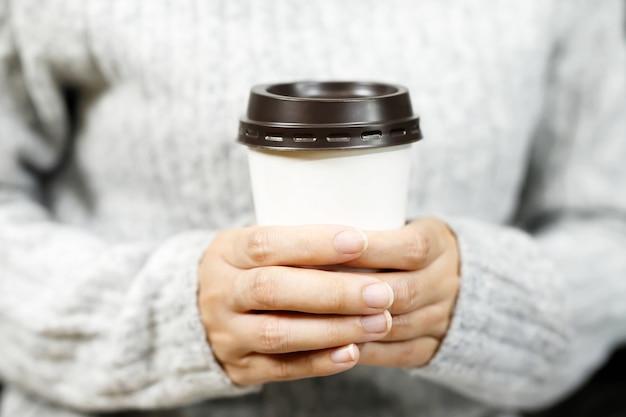 Femme tenant un café dans un café
