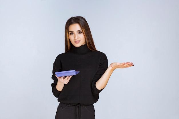 Femme tenant une calculatrice bleue et travaillant dessus.